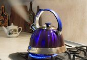 picture of boiling water  - Blue kettle with a signal of boiling water and steam jet from the spout is on the burning gas stove - JPG
