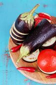 picture of brinjal  - Chopped aubergines with tomatoes and chilly pepper on cutting board on wooden background - JPG