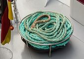 stock photo of coil  - Coiled old and worn rope on deck of cruise boat ready to tie the ship at the next dock - JPG