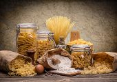 foto of traditional  - Still life with various traditional italian pasta on rustic wooden board - JPG