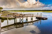 pic of inlet  - After a morning storm a rainbow reflects on the waters of a marshy inlet - JPG