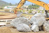 stock photo of extend  - Large rocks needing to be broken up at a construction site to extend an airport runway.