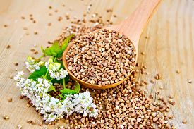 stock photo of buckwheat  - Buckwheat in a spoon with white flower buckwheat on a wooden boards background - JPG