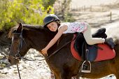 picture of year horse  - sweet beautiful young girl 7 or 8 years old riding pony horse hugging and smiling happy wearing safety jockey helmet posing outdoors on countryside in summer holiday - JPG