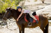 pic of horse girl  - sweet beautiful young girl 7 or 8 years old riding pony horse hugging and smiling happy wearing safety jockey helmet posing outdoors on countryside in summer holiday - JPG