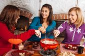 picture of dipping  - Photo of three beautiful females dipping bread into the melted cheese in a fondue pot - JPG