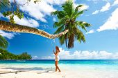 image of swing  - Woman in blue dress swinging at tropical beach - JPG