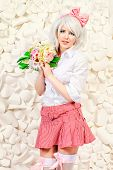 picture of wig  - Lovely girl wearing white wig and white blouse with plaid skirt posing over  background of white paper flowers - JPG