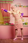 stock photo of superhero  - Funny superhero muscular man in an apron in the pink kitchen - JPG