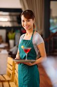 foto of serving tray  - Pretty smiling waitress holding cocktail on serving tray - JPG