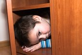 foto of wardrobe  - Scared child boy hiding in the wardrobe - JPG