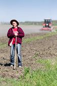 stock photo of hoe  - Senior peasant with hoe standing on farmland tractor in background - JPG