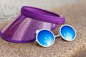 stock photo of beside  - Sun visor and sunglasses beside a swimming pool - JPG