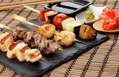foto of soy sauce  - Grilled Salmon Octopuses Shrimps and Vegetables on Wooden Stick with Ginger Soy Sauce and Wasabi closeup on Straw Mat background - JPG