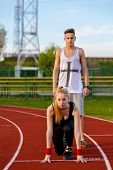 foto of competing  - Young sport couple in starting position prepared to compete and run - JPG