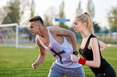 image of competing  - Young sport couple in starting position prepared to compete and run - JPG