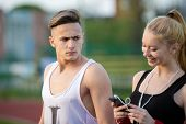 picture of she-male  - jealous worried man peering over the shoulder of his girlfriend while she is talking on the phone smiling - JPG