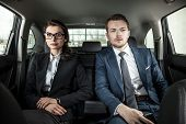 picture of limousine  - businessman and businesswoman sitting in a limousine - JPG