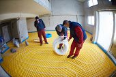 picture of convection  - grouo of workera installing underfloor heating and colling in modern home - JPG