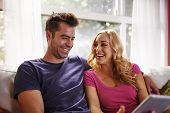 image of futon  - happy couple using table on couch together - JPG