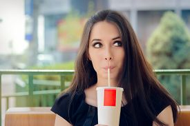 picture of cold drink  - Portrait of a funny girl drinking trough a straw - JPG