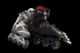 stock photo of inline skating  - 2 pairs of black and silver rollerblades isolated on black - JPG