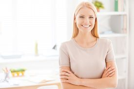 stock photo of adults only  - Beautiful young woman keeping arms crossed and smiling while standing near her working place in office - JPG