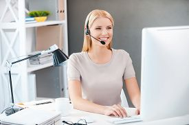 stock photo of secretary  - Beautiful young woman in headset working at the computer and smiling while sitting at her working place in office - JPG