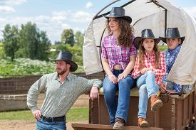 stock photo of wagon  - cowboy family of four in a wagon - JPG