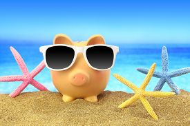 foto of starfish  - Summer piggy bank with sunglasses and starfishes on beach - JPG