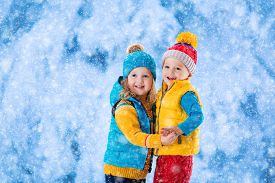 pic of snow forest  - Little girl and boy in yellow and blue knitted hat catching snowflakes in winter park on Christmas eve - JPG