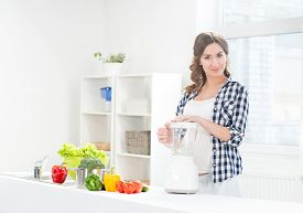 picture of blender  - Beautiful pregnant smiling woman cooking with a blender - JPG