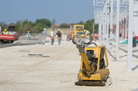 stock photo of vibration plate  - Vibrating plate compactor standing on gravel ground at construction site - JPG