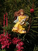 picture of cherubim  - christmas ornaments in tree; berries & angel in yellow gown playing lute