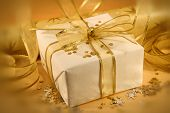 picture of gift wrapped  - christmas gift wrapped with white and gold paper and bow - JPG