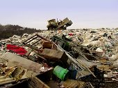 stock photo of landfills  - bulldozer at landfill shoveling garbage that is piled up - JPG
