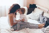 Young mother with her 2 years old little son dressed in pajamas are relaxing and playing in the bed  poster