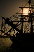 image of pirate ship  - a picture of an old sailing ship with the sun setting behind her - JPG