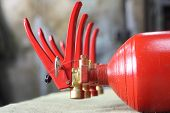 stock photo of fire extinguishers  - Four fire extinguishers are in a row on the table - JPG