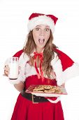 stock photo of santa claus hat  - A young mrs Santa is holding a glass of milk and a plate of cookies - JPG