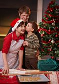 picture of nuclear family  - Young boy kissing mum on cheek for baking christmas cake dad watching smiling - JPG