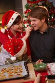 foto of nuclear family  - Smiling wife handing christmas cake to father to taste kid watching - JPG