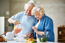 stock photo of blender  - Affectionate senior couple making fruit smoothie in blender - JPG