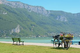 picture of annecy  - Bicycle parked in beach near mountains in Annecy - JPG