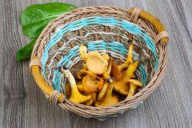 image of chanterelle mushroom  - Chanterelle mushroom in the basket on wood background - JPG