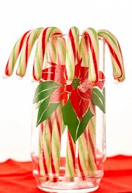 pic of poinsettia  - Drinking glass decorated with poinsettia and filled with Christmas Candy Canes against white background. Vertical with copy space. ** Note: Shallow depth of field - JPG