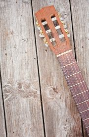 image of nylons  - Nylon string acoustic guitar neck and headstock on weathered boards - JPG