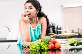foto of indian apple  - Indian woman eating healthy apple in her kitchen - JPG