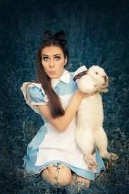 stock photo of bunny costume  - Portrait of a surprised girl in a blue costume holding a white bunny - JPG