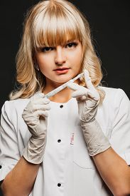 pic of scalpel  - Nurse woman doctor in a white lab coat holding a scalpel - JPG